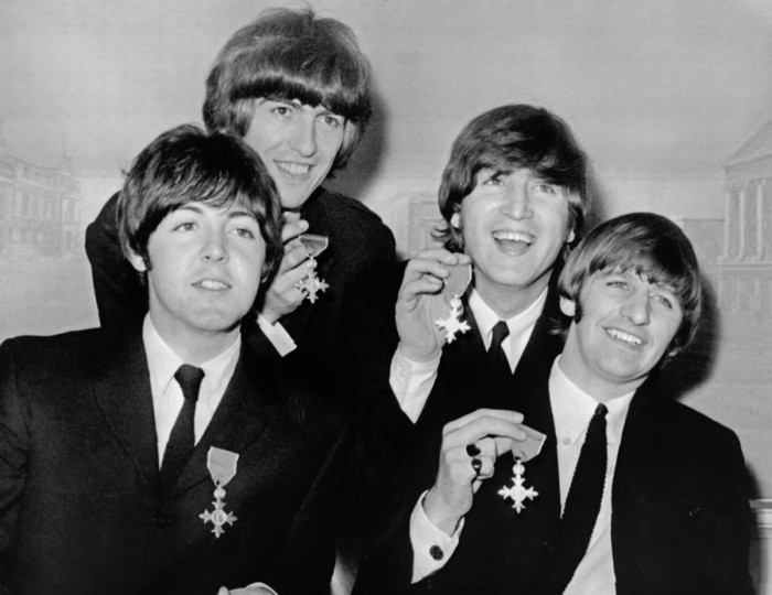British band The Beatles (from Left), Paul McCartney, George Harrison, John Lennon and Ringo Starr hold up their MBE (British Empire Medal) awards at news conference following their investiture on October 26, 1965 at Buckingham Palace in London. (Peter Skingley/Getty Images)