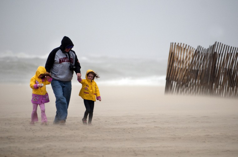 West Ocean City residents Julianna Wooden, 5, left, her father Tom Wooden and her sister Olivia Wooden, 4, are pelted with wind and sand as they make their way across the beach in Ocean City at Division Street. (Grant L. Gursky/Daily Times)