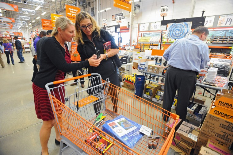 Shelley Ryan Horten, left, of Federal Hill, and Susan VanAlphen, of Parkville, call another friend to see if she needs any emergency supplies while they and Carl Francioli, right, of Baltimore, pick up emergency supplies such as flash lights and batteries at the Home Depot store on Eastern Avenue to prepare for the weekend arrival of Hurricane Sandy. (Kenneth K. Lam/The Baltimore)