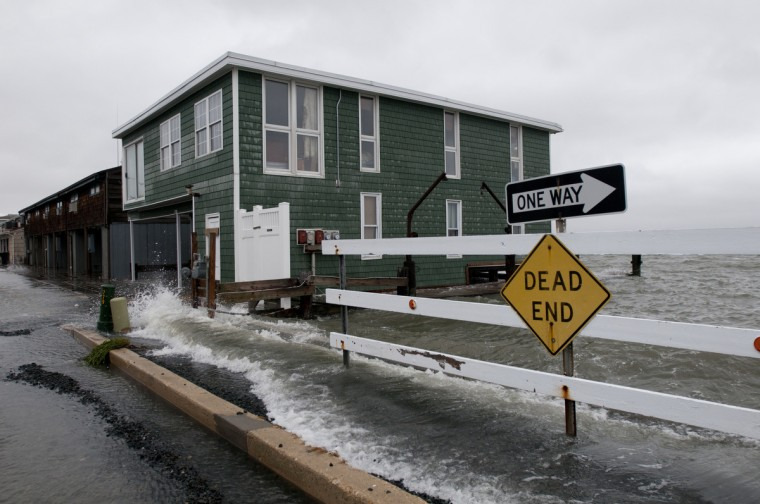 Water from the Assawoman Bay laps over the sidewalk along Edgewater Ave in Ocean City Sunday afternoon. (Grant L. Gursky/Daily Times)