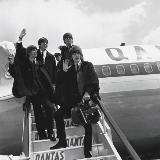 The Beatles (L to R) Ringo Starr, Paul McCartney, John Lennon and George Harrison wave to fans July 2, 1964 as they return to London from a tour of Australia. (Getty Images)