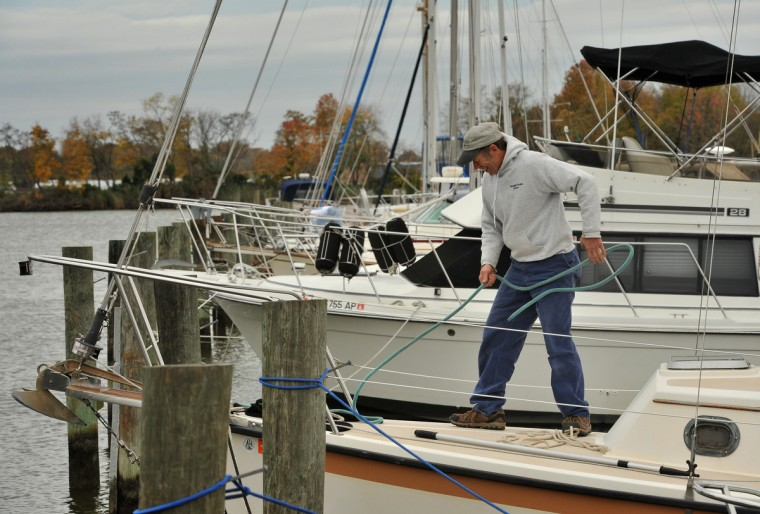 "Jay Wilson of Harrisburg, PA adds extra lines to his boat, the ""Hakuna Matata,"" after taking off the sails and taking other measures to secure it at the Maryland Marina on Frog Mortar Creek in advance of Hurricane Sandy. (Amy Davis/Baltimore Sun)"