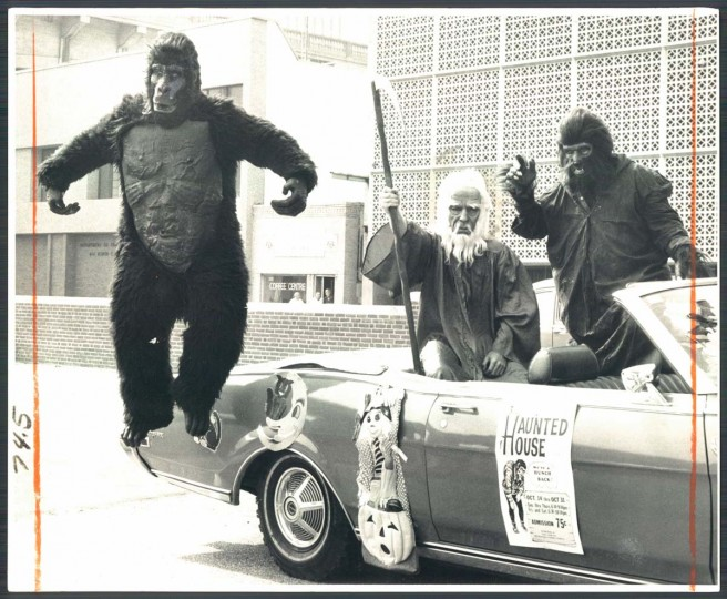 Looking a little less ferocious than King Kong, Ed Morrison as a gorilla pirouettes at left, while the grim reaper, Joe McDaniels and Wolfman Gordy Willie adopt the appropriate scary expressions as they go about town touting a haunted house open in the evening through Halloween night at Merritt Point Park, Dundalk. Oct. 16, 1974. (Weyman Swagger/Baltimore Sun)