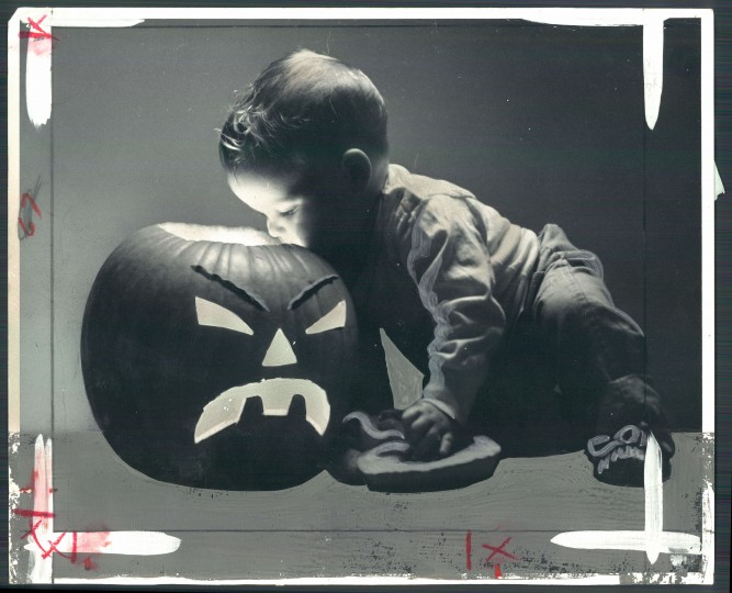 The inside of a Halloween pumpkin carved by his father intrigues two-year-old Davis Cox. Oct. 30, 1965. (Baltimore Sun)