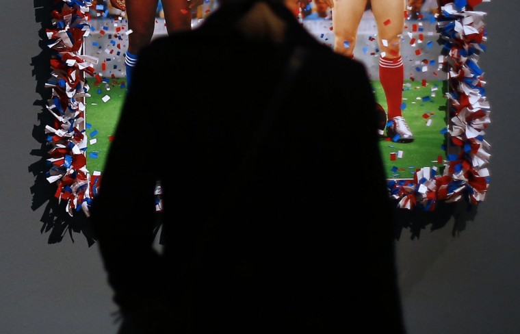 A woman looks at an artwork by French artist duo Pierre et Gilles (Pierre Commoy and Gilles Blanchard) entitled 'Vive la France (Long Live France),' as part of the 'Nackte Maenner' (Nude Men) exhibition at the Leopold Museum in Vienna, on October 18, 2012. (Alexander Klein/AFP/Getty Images, cropping by The Baltimore Sun)