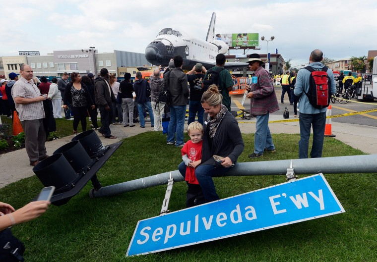 One of hundreds of street signs temporarily removed for the 12-mile road trip of space shuttle Endeavour is used as prop as a family gets their picture taken with the orbiter parked in a mall parking lot in Los Angeles, California. (Kevork Djansezian/Getty Images)