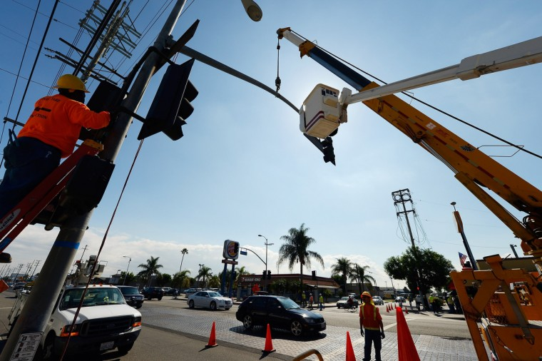 Workers prepare to bring down a street light temporarily to make room for the space shuttle Endeavour's 12-mile two-day road trip through the streets of Los Angeles County. (Kevork Djansezian/Getty Images)