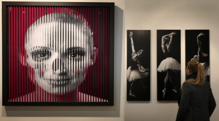 A kinetic art photographic combination print of a model's face and a skull entitled 'La Vie en Rose' (L) by artist Fred Benoit is shown at The Affordable Art Fair in Battersea Park in London, England. The autumn 2012 edition of Affordable Art Fair Battersea takes place over four days from 25-28, October and features a diverse range of contemporary art, priced between £40 - £4,000 GBP, by established and emerging artists. (Peter Macdiarmid/Getty Images)