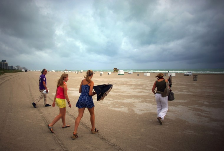 October 25, 2012: (L-R) William Rath, Julie Rath, Weera Rath and Laura Rath, on vacation from the Netherlands, walk on the beach as they are buffeted by high winds of the outer bands of Hurricane Sandy in Miami Beach, Florida. (Joe Raedle/Getty Images)