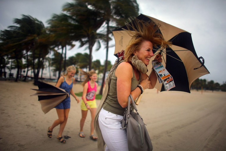 October 25, 2012: Laura Rath, on vacation from the Netherlands, walks on the beach with her family as they are buffeted by high winds of the outer bands of Hurricane Sandy in Miami Beach, Florida. (Joe Raedle/Getty Images)