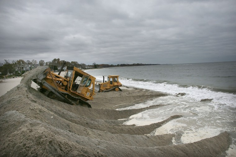 Earth movers build protective berms on Compo Beach as the first signs of Hurricane Sandy approaching Westport, Connecticut. The storm, which could affect tens of millions of people in the eastern third of the U.S., is expected to bring days of rain, high winds and possibly heavy snow in parts of Ohio and West Virginia. New York Governor Andrew Cuomo announced that New York City will close its bus, subway and commuter rail service Sunday evening ahead of the storm. (Spencer Platt/Getty Images)