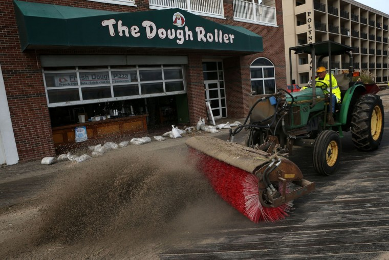 October 30, 2012: A member of the cleanup crew brushes up the dirt that was left on the boardwalk after Hurricane Sandy had hit the region in Ocean City, Maryland. (Alex Wong/Getty Images)