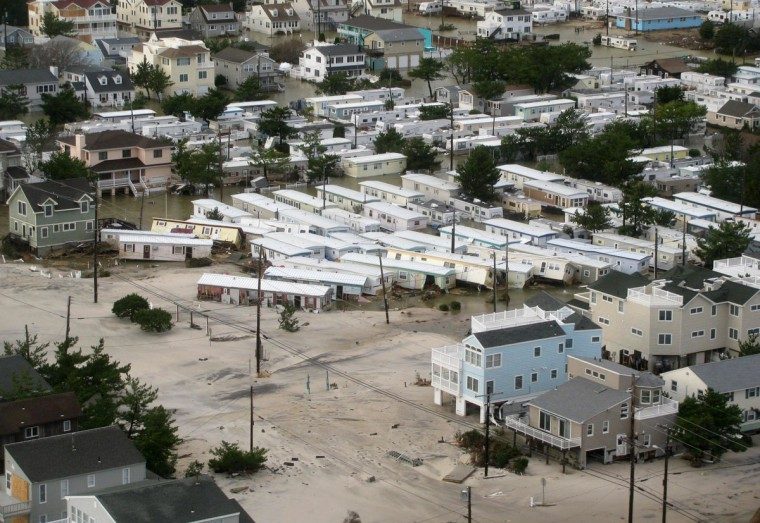 A helicopter from Coast Guard Air Station Atlantic City observes displaced homes on the New Jersey coastline. The storm has claimed many lives in the United States and has caused massive flooding across much of the Atlantic seaboard. (U.S. Coast Guard via Getty Images)