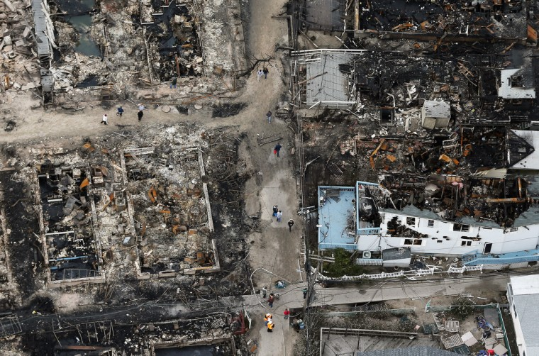 People walk through the remains of burned homes after Hurricane Sandy in the Breezy Point neighborhood of the Queens borough of New York City. Over 50 homes were reportedly destroyed in a fire during the storm. (Mario Tama/Getty Images)