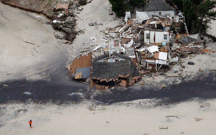 A woman walks on the beach past homes destroyed by Hurricane Sandy in Mantoloking, New Jersey. (Mario Tama/Getty Images)