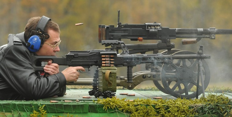 Russia's Prime Minister Dmitry Medvedev fires a machine gun as visits a weapons factory in Klimovsk outside Moscow. (Alexander Astafyev/GettyImages)