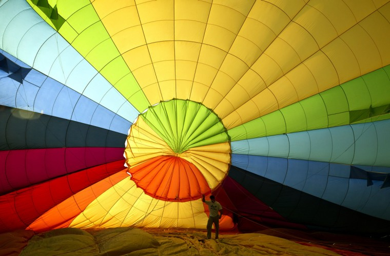 A participant of a hot air balloon festival prepares a balloon for a flight over the Neguev desert in Timna Valley national park, southern Israel. (Jack Guez/GettyImages)
