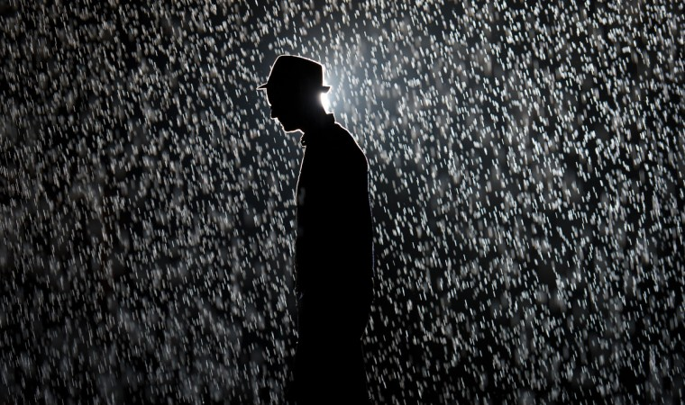 """A man poses for pictures as he walks through an art installation entitled """"Rain Room"""" during a photocall at the Barbican in London. The 'Rain Room' is a 100 square meter field of falling water which visitors are invited to walk into. As the visitor walks through the rain stops around them, giving them an experience of how it might feel to control the rain. The installation opens to the public on October 4, (Leon Neal/GettyImages)"""