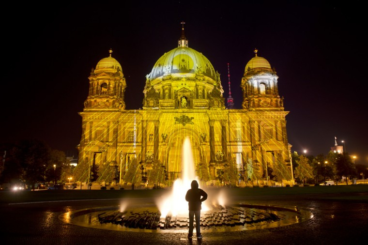 "A man stands in front of the Cathedral of Berlin (Berliner Dome) while it is illuminated as the technicians test the the lights on the eve of the opening of the ""Festival of light"" in the German capital. The yearly festival see famous buildings and landmarks being used as canvas for light installations. (Odd Andersen/GettyImages)"