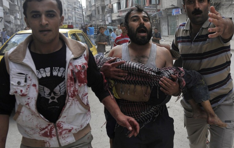 A Syrian man carries the body of his five-year-old son Mohammed Mustafa outside a hospital following shelling by Syrian government forces during battle with rebel fighters in the northern city of Aleppo. Syrian rebels took control of Maaret al-Numan, a strategic Idlib province town on the highway linking Damascus with second city Aleppo, said the Syrian Observatory for Human Rights. (Tsauseef Mustafa/GettyImages)