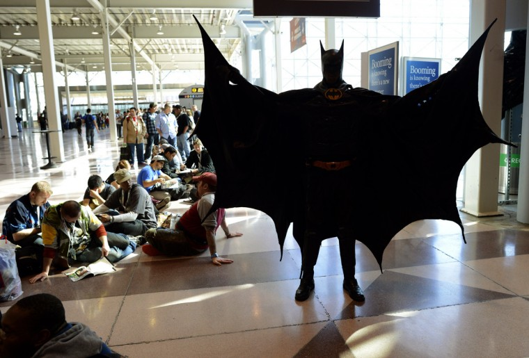 A man dressed as Batman waits with other fans. (Timothy Clary/Getty Images)