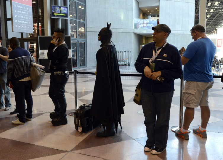 A man dressed as Batman waits with other fans during the opening session of the 2012 New York Comic Con at the Jacob Javits Center. (Timothy Clary/Getty Images)