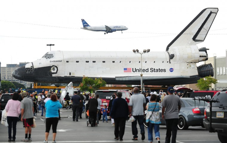 An aircraft flies overhead as people gather for a closer view of US space shuttle Endeavour during its nine-hour holding point at a parking lot while on its final journey through city streets to a permanent home at the California Science Center. (Frederic J. Brown/Getty Images)