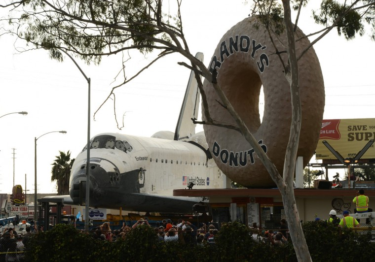 The Space Shuttle Endeavour stops in front of the iconic Randy's Donuts shop as it travels through the streets of Los Angeles on its final journey to its permanent museum home. (Robyn Beck/GettyImages)
