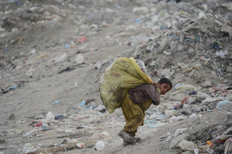 A young Afghan garbage collector carries recyclable material from a landfill in the outskirts of Kabul. Over a third of Afghans are living in abject poverty, as those in power are more concerned about addressing their vested interests rather than the basic needs of the population, a UN report said. (Jawad Jalali/Getty Images)