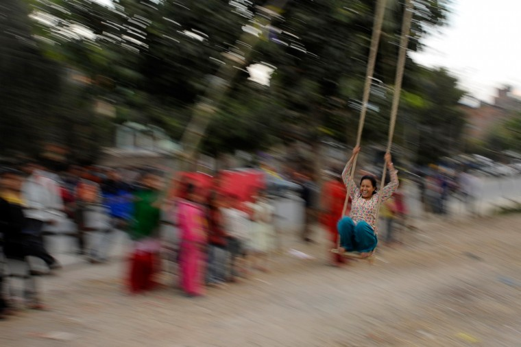 "Nepalese youth play on a swing popularly known as ""Dashain Ping"" in Kathmandu the second day of the Hindu festival of Dashain. People of all ages play on a swing in towns and villages while celebrating the biggest Hindu festival Dashain, which is celebrated for fifteen days in honour of the Hindu goddess of power Durga. (Prakash Mathema/Getty Images)"