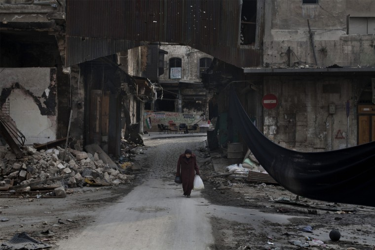 "An elderly Syrian woman crosses a street next to a long black cloth used to separate the area from Syrian government forces' snipers fire, in the Bab el-Adid district in Aleppo. UN-Arab League envoy Lakhdar Brahimi is pushing ""extremely hard"" for a ceasefire in Syria and will brief the UN Security Council on Wednesday on his efforts, the UN spokesman said. (Favio Bucciarelli/Getty Images)"
