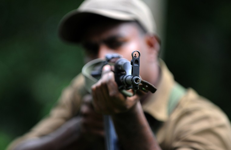 An ethnic Tamil Sri Lankan police recruit aims his assault rifle at a police training college in Kalutara, near the capital Colombo. A group of 480 ethnic Tamil men and women have been recruited for service amid calls from minority Tamil parties to increase the number of Tamil police in a force dominated by the majority Sinhalese. (Ishara S. Kodikara/Getty Images)