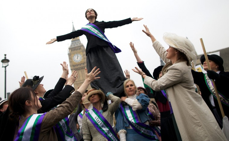 Feminists dressed as The Suffragettes pose during a photo call at Parliament Square following a protest for women's rights in London. (Andrew Cowie/Getty Images)