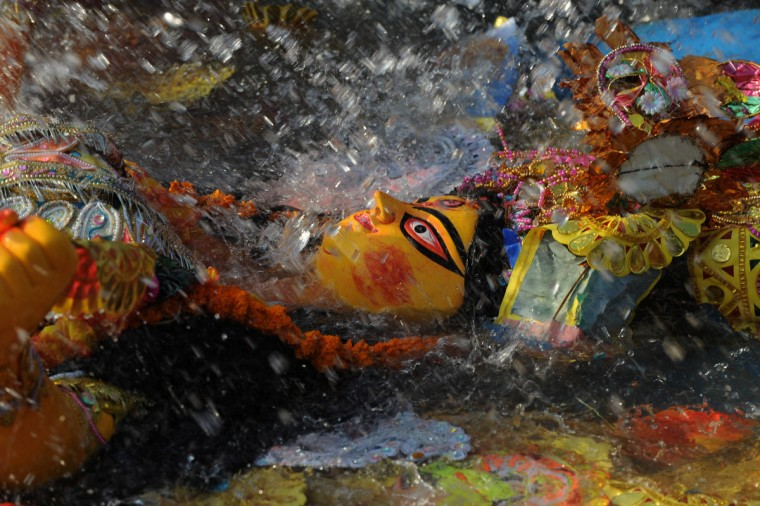 An idol of the goddess Durga is immersed during the Vijaya Dashami or Dusshera Festival in Siliguri on the final day of Durga Puja. The five-day Durga Puja festival which began on October 20 culminates on October 24 with the immersion of idols in water bodies and symbolises the victory of good over evil. (DiptenduDutta/Getty Images)