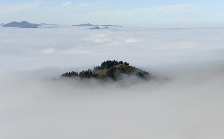 A hill is covered in fog, seen from the 1,838 meters high Wendelstein mountain in the Alps near Bayrischzell, southern Germany. Meteorologists forecast unsettled weather with morning fog and rain for the upcoming weekend in southern Germany. (Christof Stache/Getty Images)