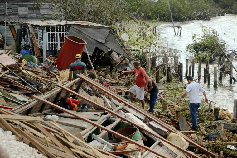 Cubans tries to recover belongings from a their destroyed house in Antillas population, Holguin province, 750km east of Havana. Hurricane Sandy claimed 11 lives as it tore across Cuba Thursday, leaving a path of destruction in the eastern part of the island, officials in Havana said. (Getty Images)