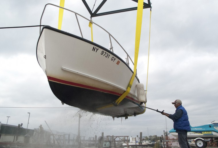 A worker at Stelter's Marine on City Island cleans the bottom of a boat as it is hauled out of the the water in New York. People across much of the northeast United States are preparing for serious and life-threatening weather conditions, as Hurricane Sandy heads north. (Don Emmert/Getty Images)