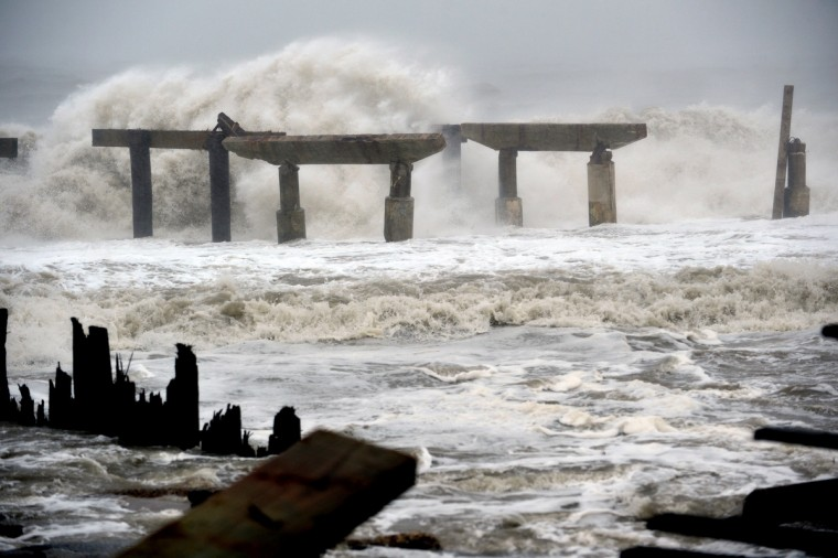 Waves crash against a previously damaged pier before landfall of Hurricane Sandy in Atlantic City, New Jersey. Storm-driven waves crashed ashore and flooded seafront communities across a swathe of the eastern United States as Hurricane Sandy barreled towards land. (Stan Honda/Getty Images)