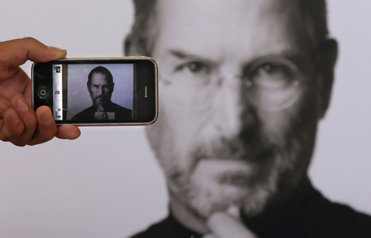 October 6, 2011: In this photo illustration a photographer takes a picture with his own iPhone of a tribute to Apple Computer co-founder Steve Jobs placed outside The Apple Store in Covent Garden in London, England. Jobs, 56, passed away after a long battle with pancreatic cancer. (Peter Macdiarmid/Getty Images)