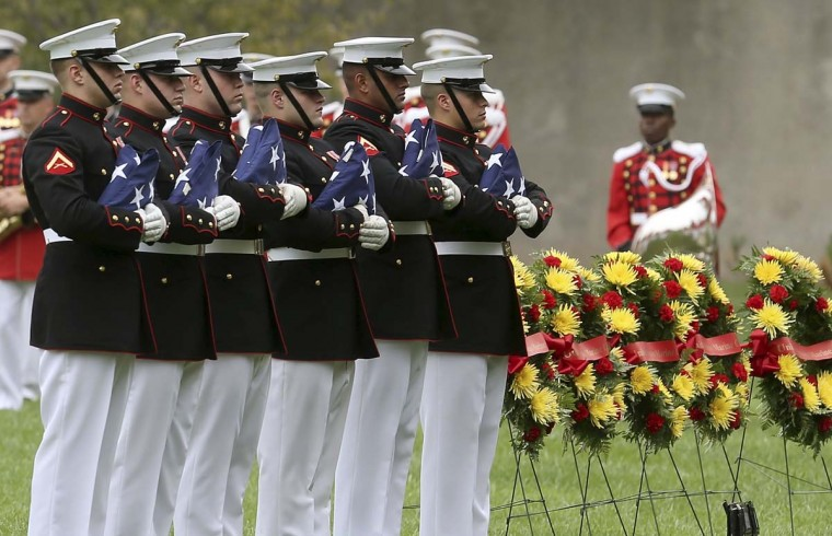 A Marine honor guard team holds seven American flags during a group burial service for seven missing U.S. Marines killed in World War II, at Arlington Cemetery in Arlington, Virginia. The Marines died when their U.S. Navy bomber went down on an island in a remote part of the South Pacific. A U.S. government survey team spent more than a decade excavating the site for bodies, military equipment and wreckage remains. (Mark Wilson/Getty Images)
