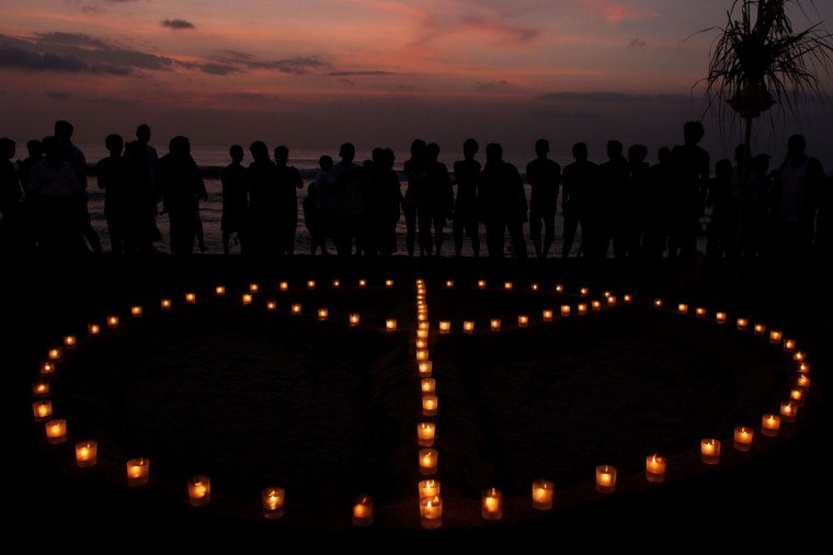 People gather around a peace sign made of candles as part of the 'Paddle for Peace' memorial ceremony on Kuta Beach, Bali in Indonesia. (Chris McGrath/Getty Images)