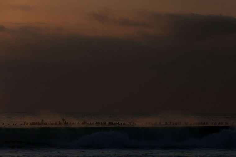 Surfers are covered by the spray from a wave as they form a tribute circle off the beach as part of the Paddle for Peace memorial ceremony on Kuta Beach, Bali in Indonesia. (Chris McGrath/Getty Images)