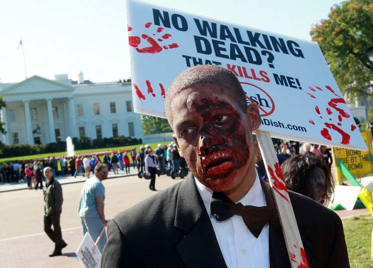 "Zombies unite on the eve of World Zombie Day in front of the White House to persuade DISH Network to return AMC and its top-rated series ""The Walking Dead"" to its line-up. (Photo by Paul Morigi/Getty Images for AMC Networks)"