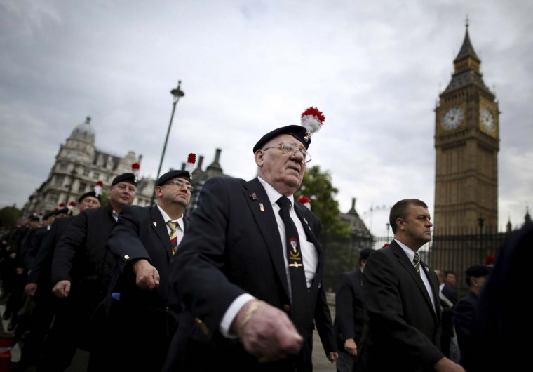 Veterans from The Second Battalion of the Royal Regiment of Fusiliers march past Parliament in London, England. Members of the regiment are protesting about defense cuts which may result in the disbandment of the unit. (Peter Macdiarmid/Getty Images)