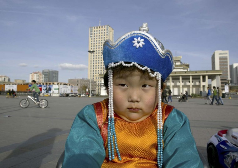 A young boy sits in a motorized toy car in Sukhbataar Square October 18, 2012 Ulaanbataar, Mongolia. (Paula Bronstein/Getty Images)