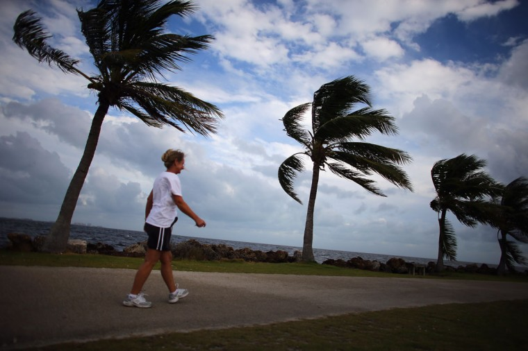 October 24, 2012: Stephanie Bilyeu walks along the ocean as blustery winds blow through the palm trees as the outerbands of Hurricane Sandy are felt in Miami, Florida. (Joe Raedle/Getty Images)
