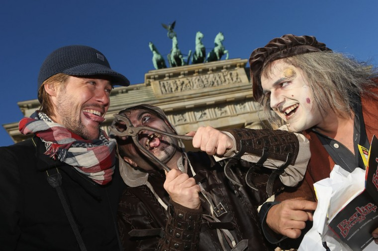 Actors pretending to be zombies from the Middle Ages threaten to pull out the tongue of another actor pretending to be a passing tourist during a small event to promote the opening of Berlin Dungeon in front of the Brandeburg Gate in Berlin, Germany. The Berlin Dungeon, an attraction of different rooms with horror themes, will open in March, 2013. (Sean Gallup/Getty Images)