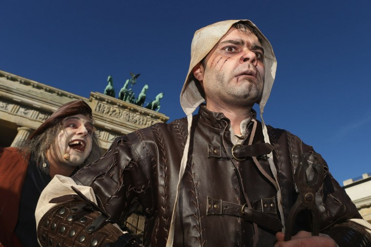 Actors pretending to be zombies from the Middle Ages arrive at the Brandenburg Gate during a small event to promote the opening of Berlin Dungeon, an attraction of different rooms with horror themes, in Berlin, Germany. (Photo by Sean Gallup/Getty Images)