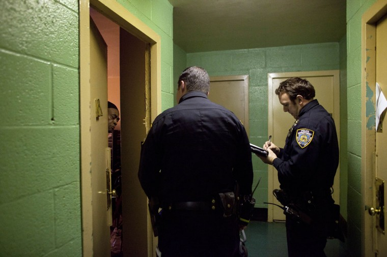 October 28, 2012: New York City police officers go door to door in a housing project to take note of which residents are ignoring the mandatory evacuation order as Hurricane Sandy approaches in the Rockaway Beach neighborhood of the Queens borough of New York City. New York City Mayor Michael Bloomberg announced a mandatory evacuation on low-lying coastal areas of the city. (Photo by Allison Joyce/Getty Images)