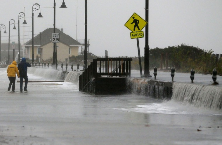 October 29, 2012: People walk across Beach Ave. as flood waters from Hurricane Sandy rush over the seawall in Cape May, New Jersey. (Mark Wilson/Getty Images)